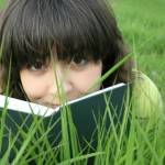 Pretty girl on the grass looking over the book