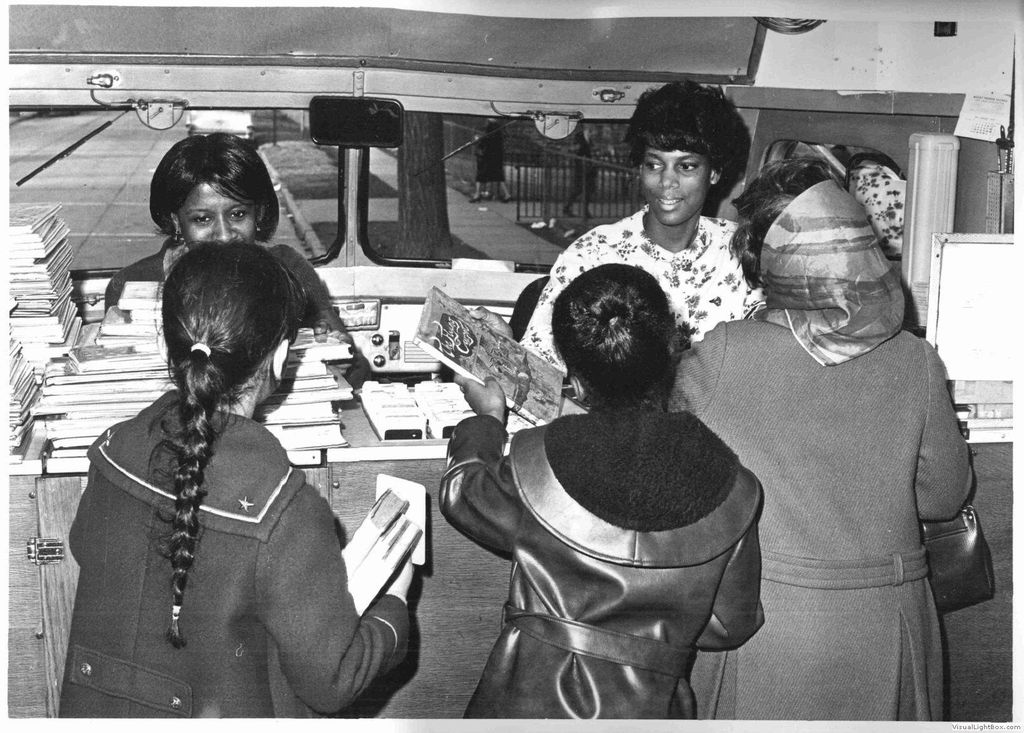 three patrons stand in front of a counter in a bookmobile with two librarians behind the counter