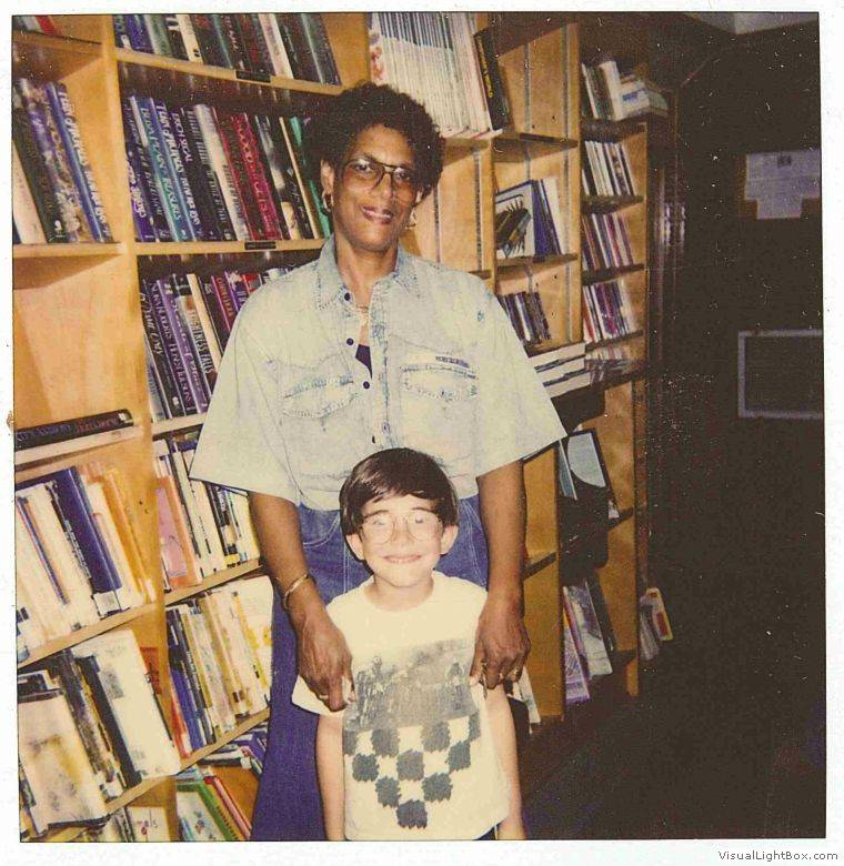 woman and child posed in front of bookmobile interior shelves