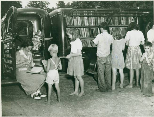 children line up in front of a bookmobile, browsing and checking out books
