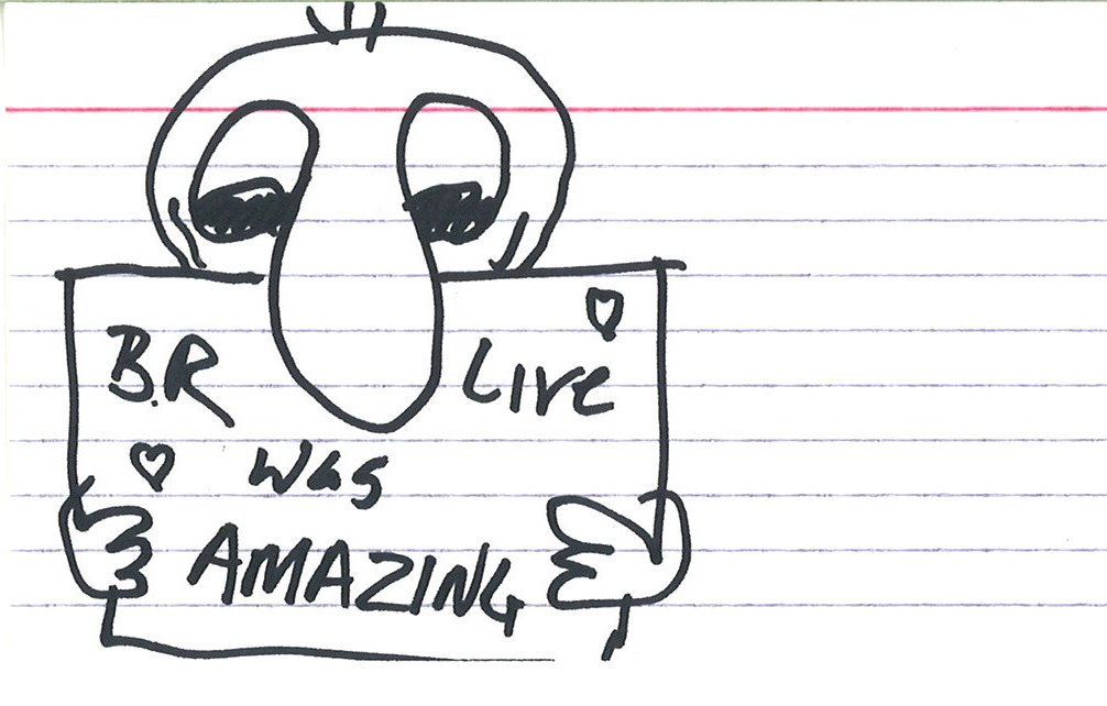 """sketch of a person holding a sign that says """"BR Live was AMAZING"""" with little hearts in the corners"""