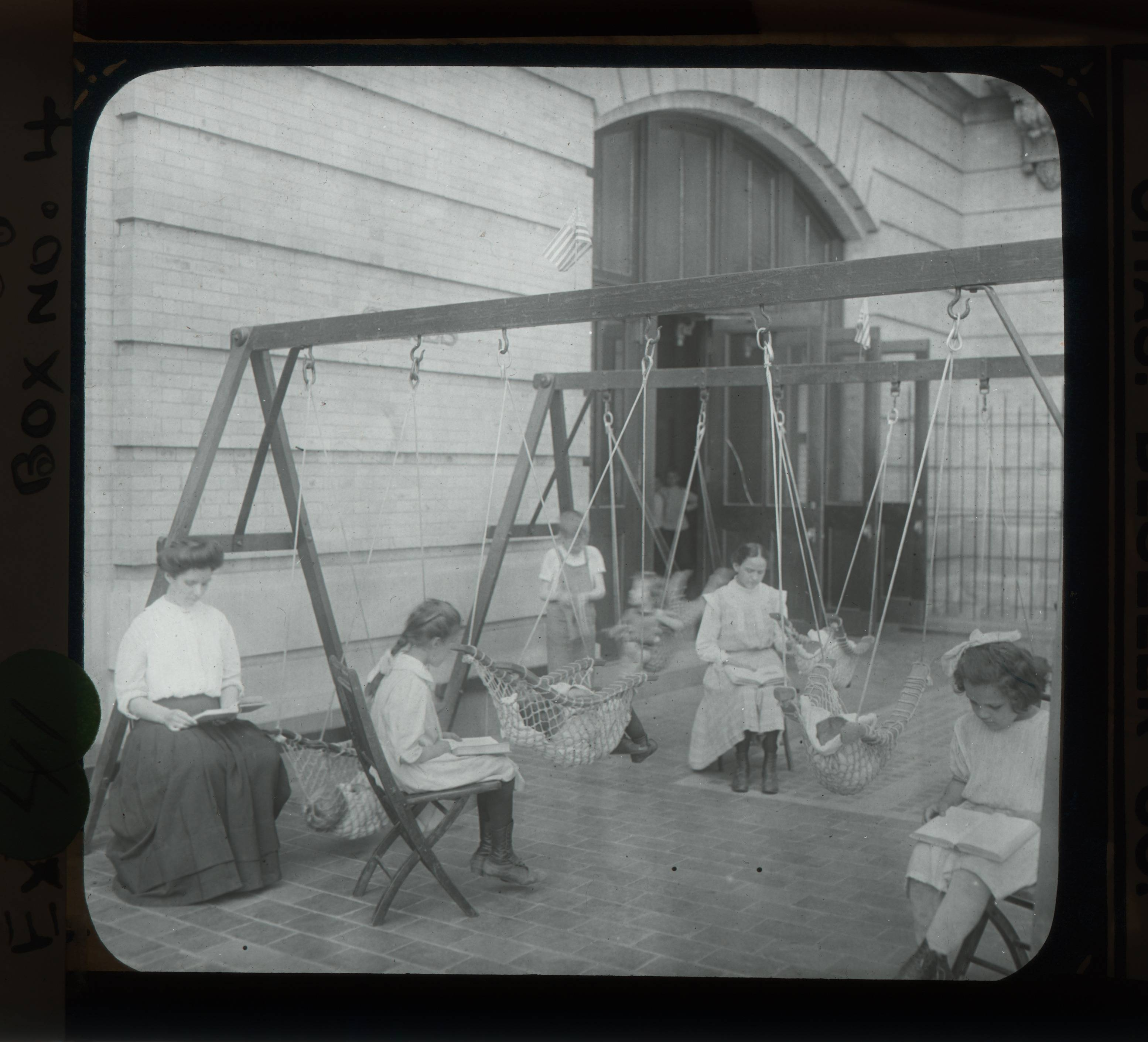 """Women and girls reading near swingset where younger children are suspended in hammock like swings, July 1910"" - Lewis Wickes Hine"