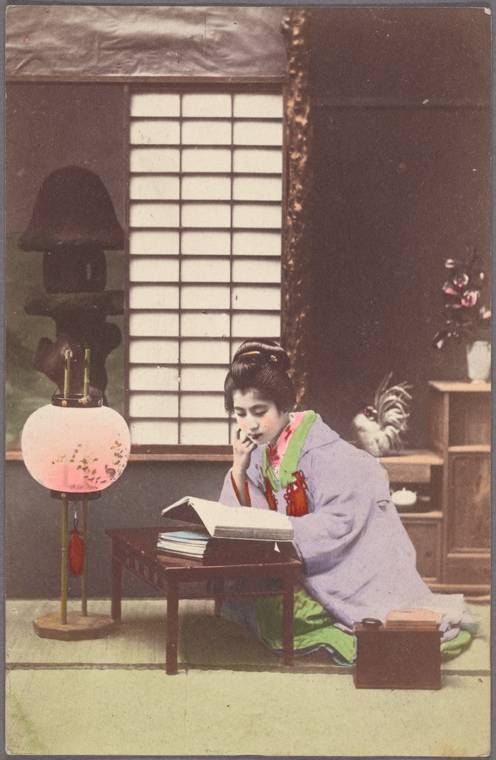 Young woman reading near lamp