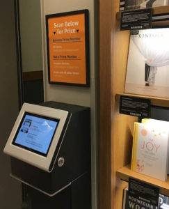 An electronic, touch screen kiosk beside a bookself. A sign above it offers instructions