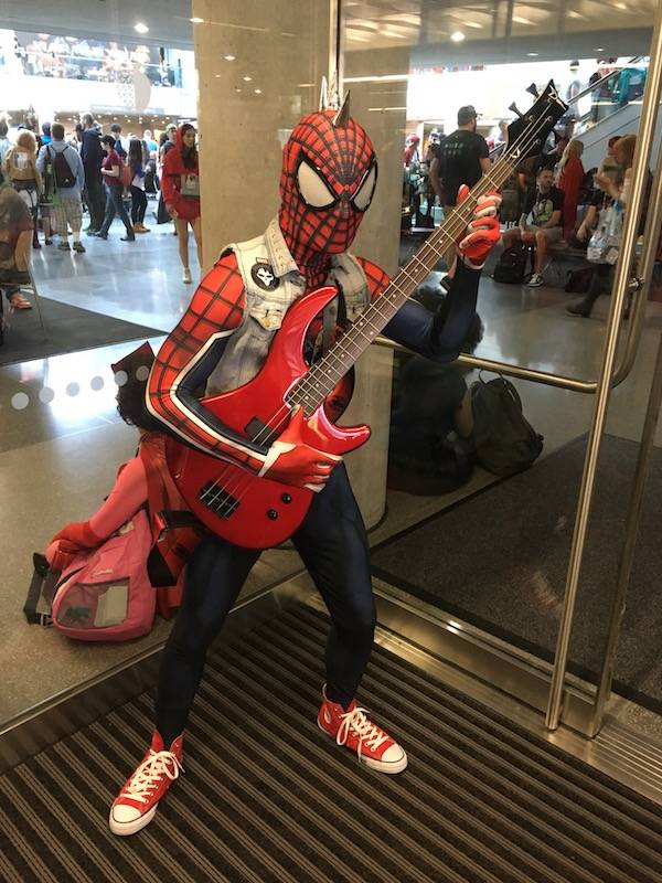 A Spider-Man cosplayer with a denim vest covered in patches, a metal-spice mohawk, red converse, holding a red guitar