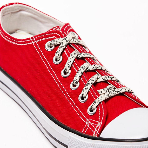 red canvas sneakers laced with shoelaces that are covered in words