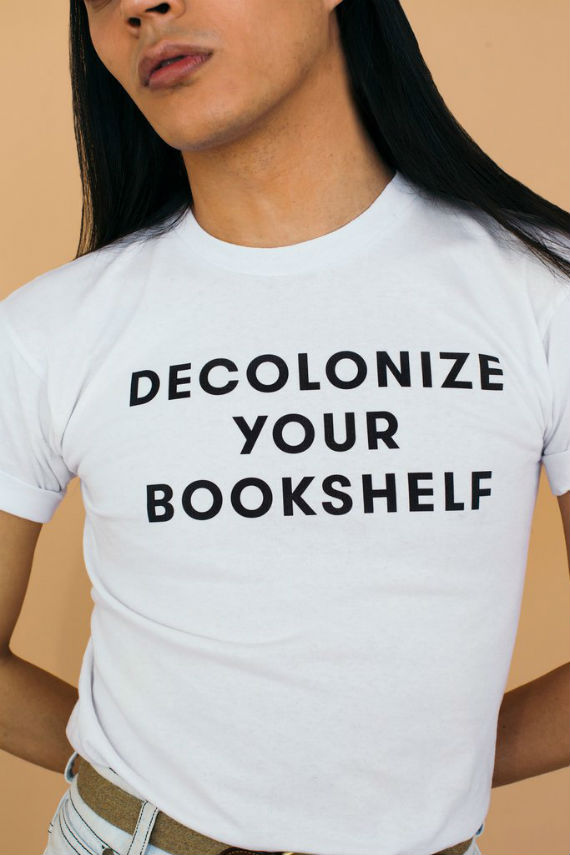 """Only a torso is visible, wearing a white t-shirt with black text that reads, """"DECOLONIZE YOUR BOOKSHELF."""""""
