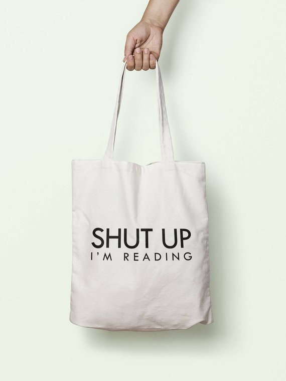 """Canvas tote bag being held by a hand. Tote has text that reads """"Shut Up I'm Reading."""""""