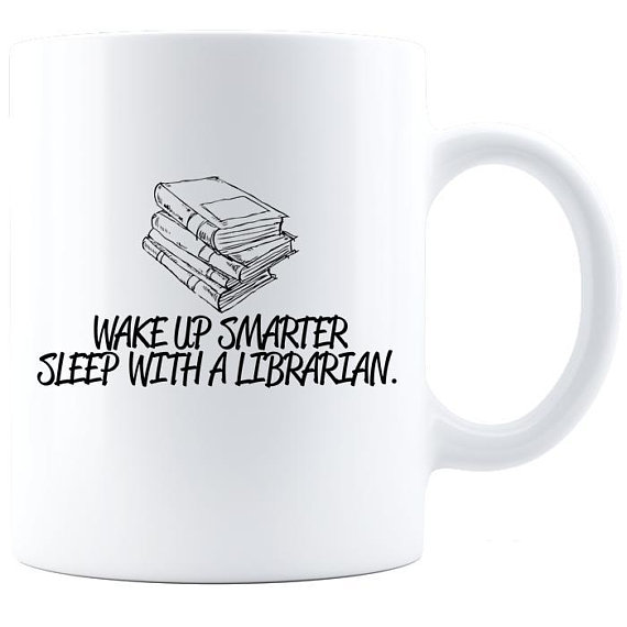 """White coffee mug with a stack of books illustrated. Under the stack, text reads, """"Wake up smarter. Sleep with a librarian."""""""