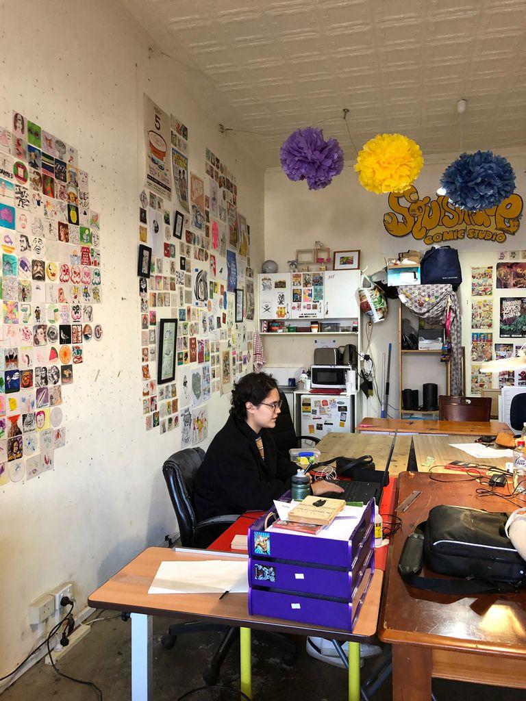 Artist working at computer in comic studio
