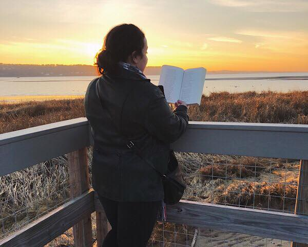 A woman reading, facing away, in front of a waterfront sunset